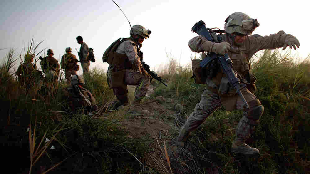 Lance Cpl. Chris Garcia crosses an irrigation ditch in Afghanistan.