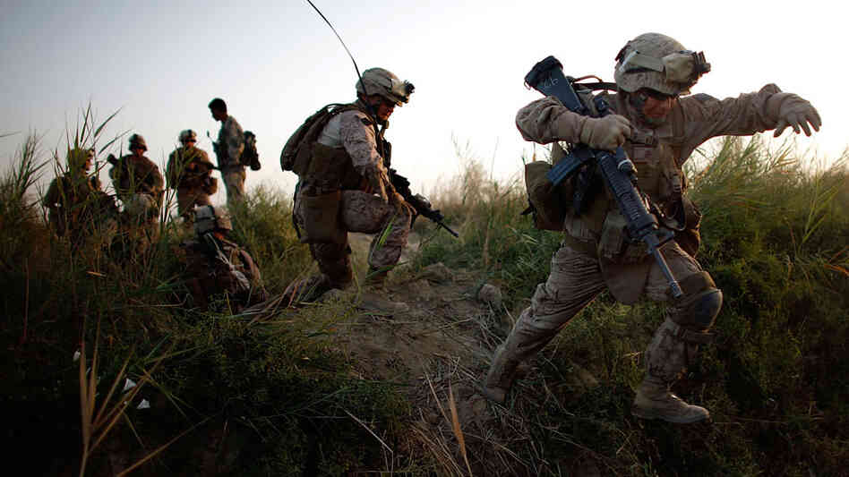 W: Lance Cpl. Chris Garcia crosses an irrigation ditch in Afghanistan.