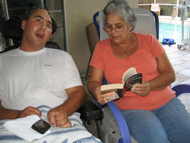 Nellie Bagley (right) reads to Jose at their Tampa home. Doctors say Jose might not perceive or understand the world any more than does a baby.