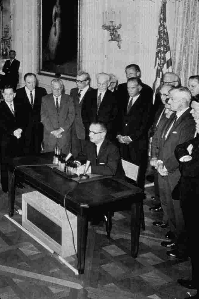 President Lyndon Johnson signs the Tonkin resolution.