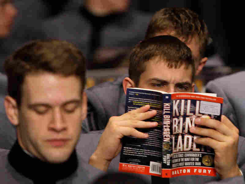 A cadet reads 'Killing Bin Laden' while waiting for President Obama to speak.