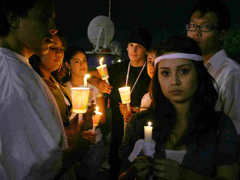 Richmond High School students hold candles during a vigil to support the victim of a brutal rape.