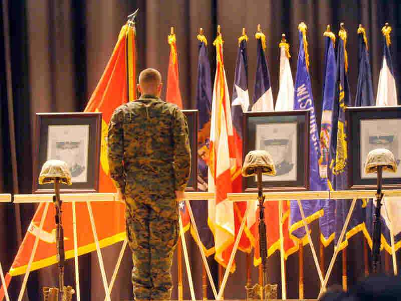 A Marine salutes portraits of the fallen. Jeff Janowski for NPR