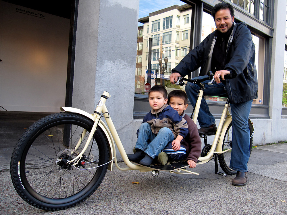 A cyclist and boys ride one of Metrofiets' cargo bikes.