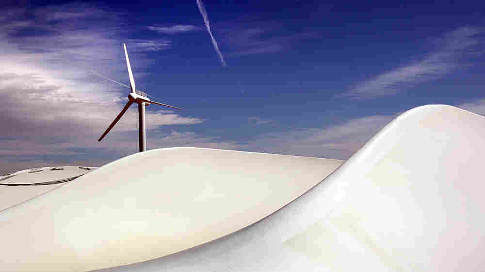 A wind turbine turns as giant blades lie awaiting new construction at NREL.