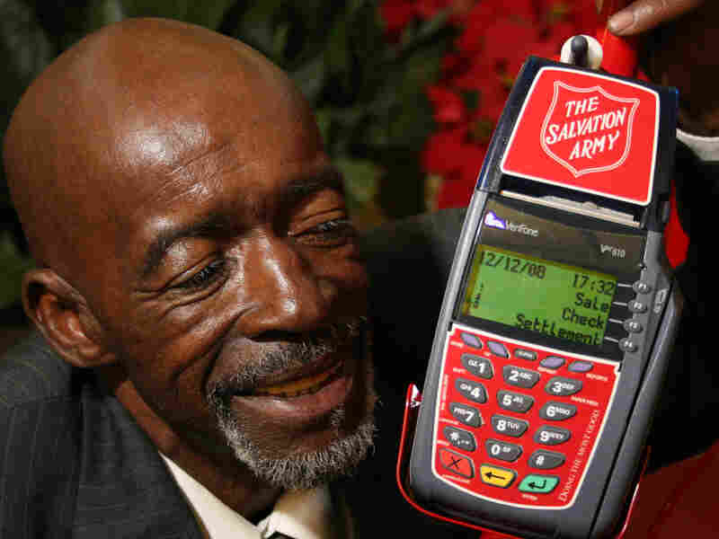 Salvation Army bell ringer Henry Oliver with a card scanner