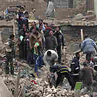 Iraqi security forces and rescuers search for survivors at the site of a bomb attack in Baghdad.