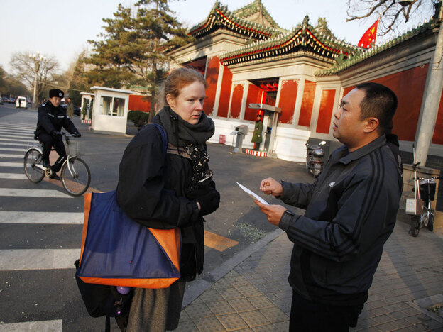 Julie Harms is questioned by a plainclothes policeman outside the Zhongnanhai compound after she attempts to deliver a letter to China's top leaders, who resides inside Zhongnanhai in Beijing. The American woman is seeking justice from the central government for her fiance, who she says was unjustly charged with a crime.