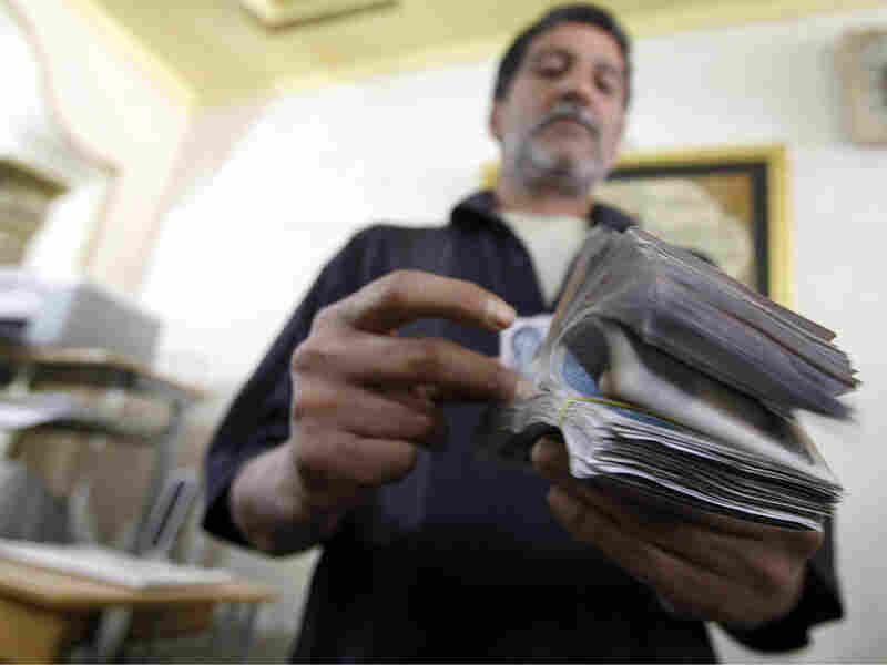 An Iraqi man counts out Iraqi dinars at a money changer in central Baghdad in May.