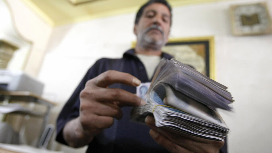 An Iraqi man counts out Iraqi dinars at a money changer in central Baghdad in May. The Iraqi economy is hampered by red tape and corruption.