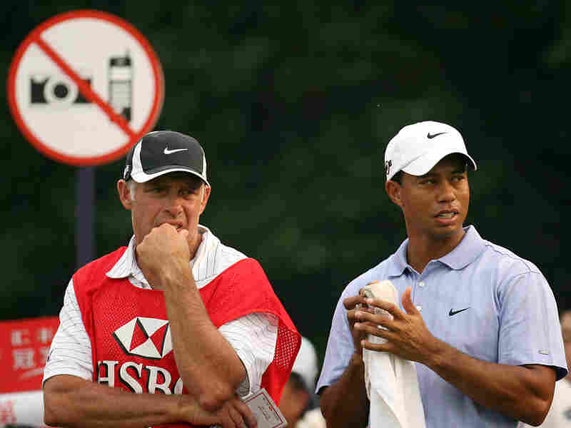 Tiger Woods on the 17th tee with a No Cameras sign behind him, in Shanghai