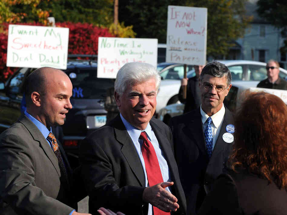 Demonstrators stand behind Sen. Chris Dodd, protesting his role in the banking crisis.