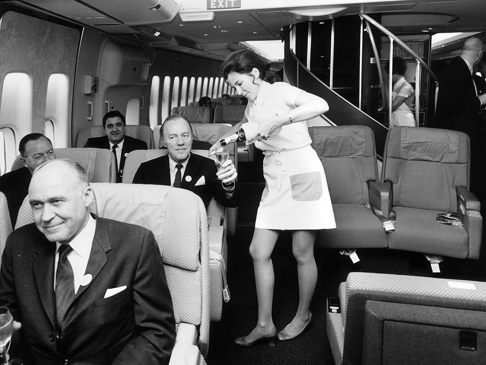 <strong>Playing Favorites:</strong> Airlines have long sought to make their first-class passengers comfortable. In this 1970 photo, a Pan Am air hostess serves champagne in the first-class cabin of a Boeing 747.