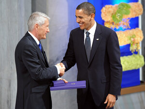 Thorbjoern Jagland hands the diploma and medal to Obama