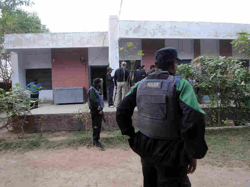 Pakistani police commandos gather outside a house where Pakistani security forces arrested five U.S.