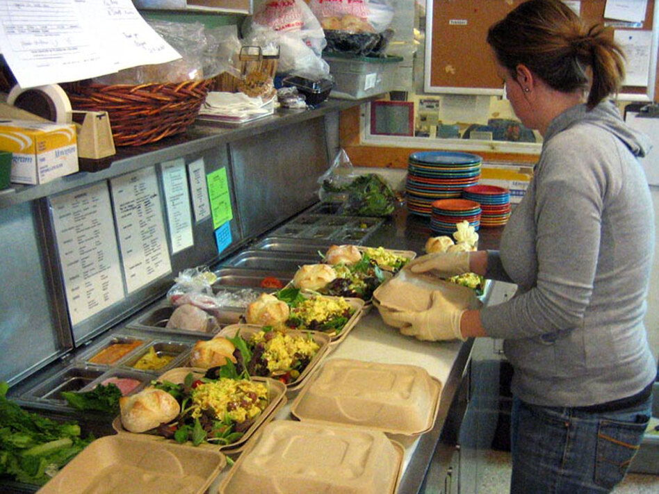 Cucina Deli server Brandi Alvarado prepares egg salad lunches for delivery to an office.