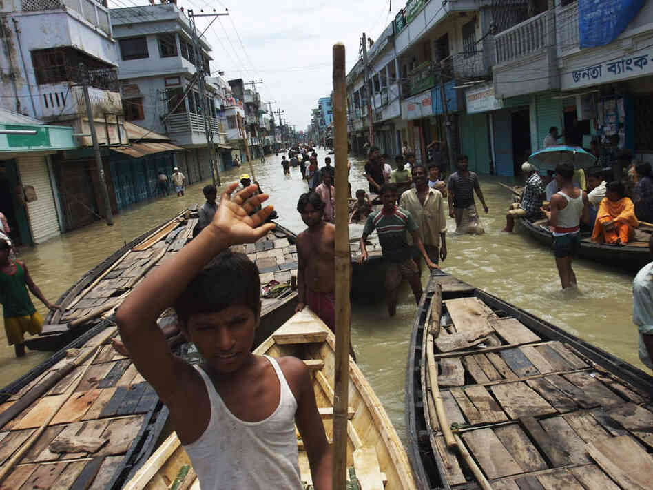 Boats vie for passengers at a flooded intersection in downtown Sirajganj, Bangladesh