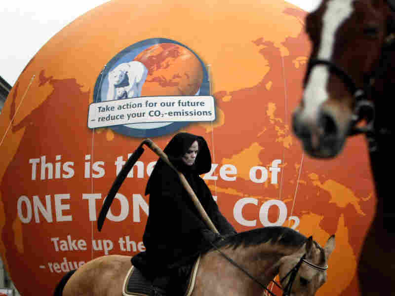 A character dressed as death on horseback holding a scythe outside parliament in Copenhagen