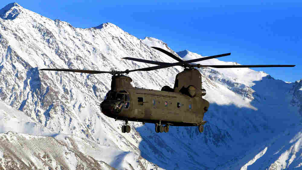 W: A U.S. Army helicopter flies over the snow-capped Hindu Kush mountains of Afghanistan