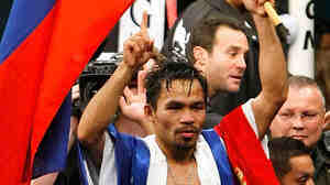 Manny Pacquiao waves the flag of the Philippines as he celebrates his victory over Oscar De La Hoya.