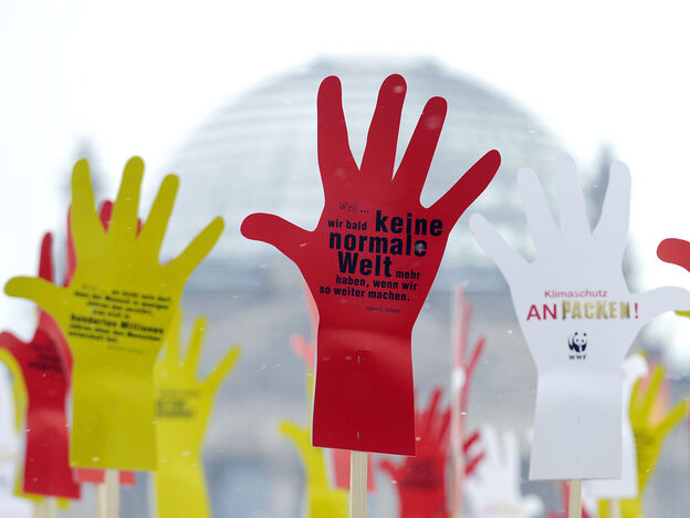 """Hand-shaped placards inscribed with the words """"Tackle climate change!"""" in Berlin."""