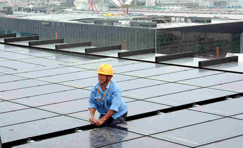 A Chinese worker installs solar panels on the rooftop