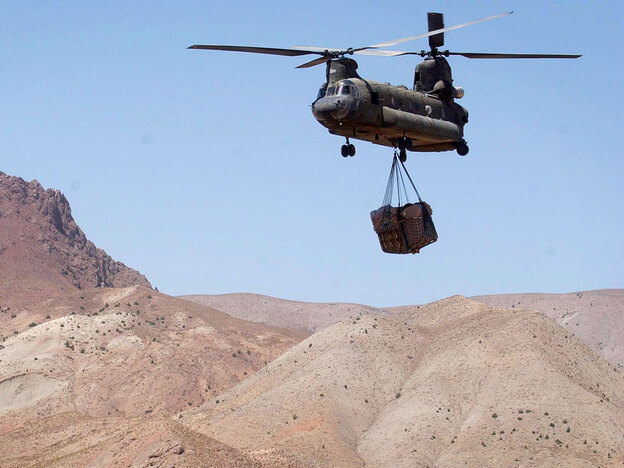 A U.S. Army Chinook helicopter carrying sling-loaded cargo flies to a forward base in Afghanistan.
