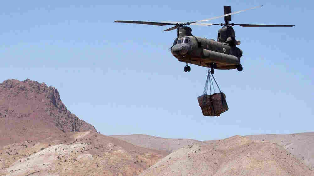 W: A U.S. Army Chinook helicopter carrying sling-loaded cargo flies to a forward base in Afghanistan