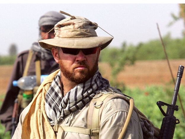 An American security contractor for DynCorp walks through an opium poppy field in Helmand province, southern Afghanistan, in 2006.