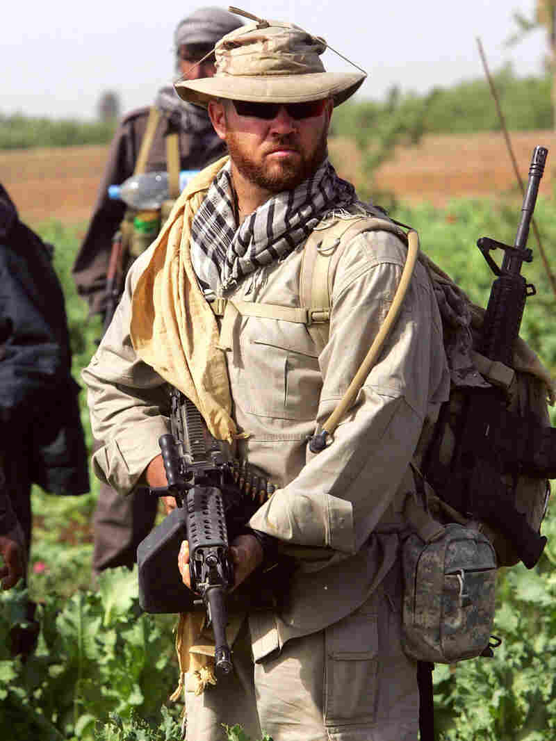 An American security contractor for DynCorp walks through an opium poppy field in Helmand province