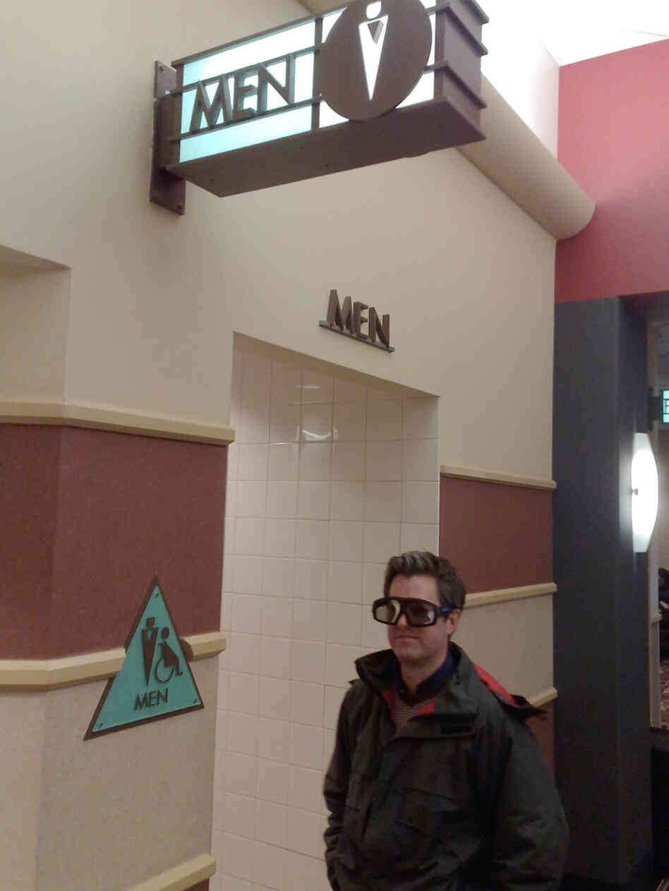A movie theater patron wears his 3D glasses in the hallway of an IMAX theater before viewing 'Avatar