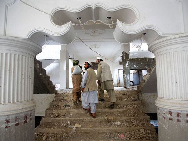 Contractors walk through an apartment complex under construction in downtown Kandahar, Afghanistan, in April.