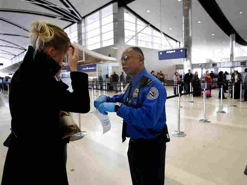 Paul Marshall of the Transportation Security Administration helps an international traveler.