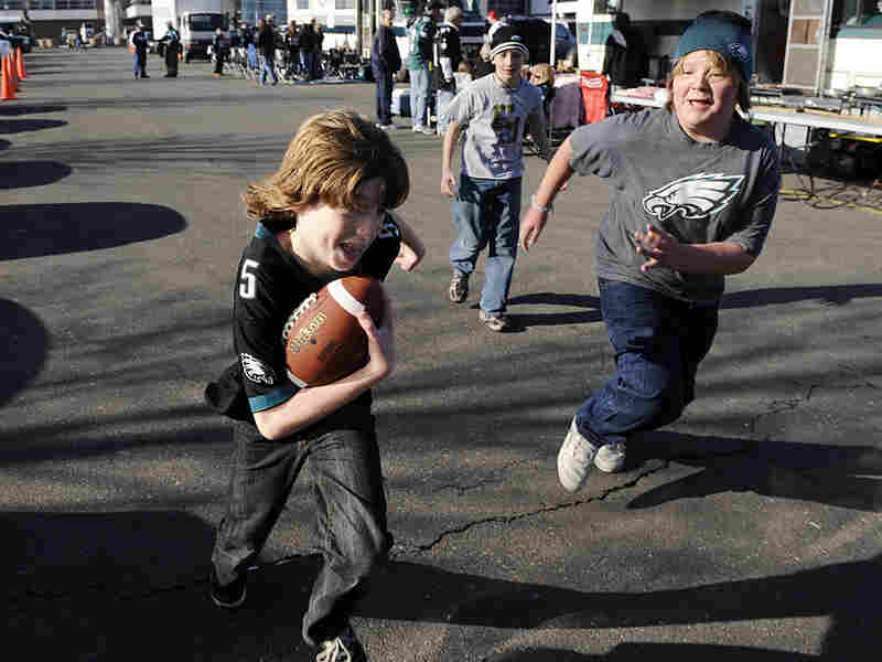 Kids playing a game of touch football in the parking lot