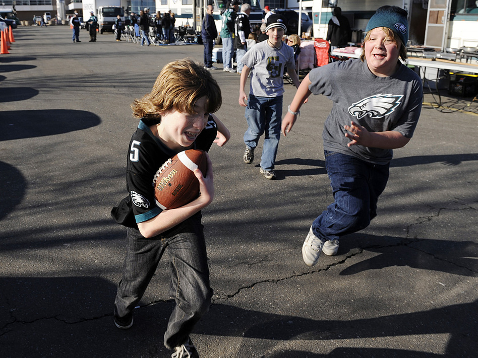 Kids playing a game of touch football in the parking lot of Lincoln Financial Field before the start of an NFL football game between the Philadelphia Eagles and the Denver Broncos Sunday, Dec. 27, 2009, in Philadelphia.