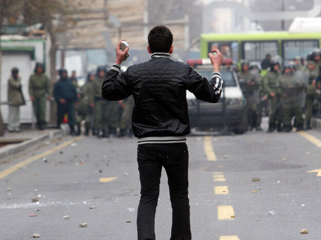 An Iranian opposition protester holds stones as he faces security forces during clashes in Tehran on Sunday. The protests, the most violent since those that followed the disputed presidential election in June, cap a year of unprecedented challenge for Tehran.