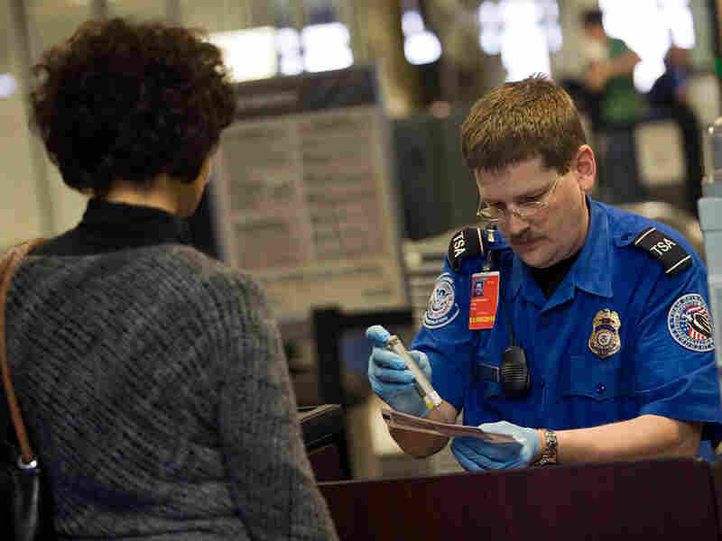 A TSA officer screens an airline passenger in Terminal C at Dallas/Fort Worth International Airport
