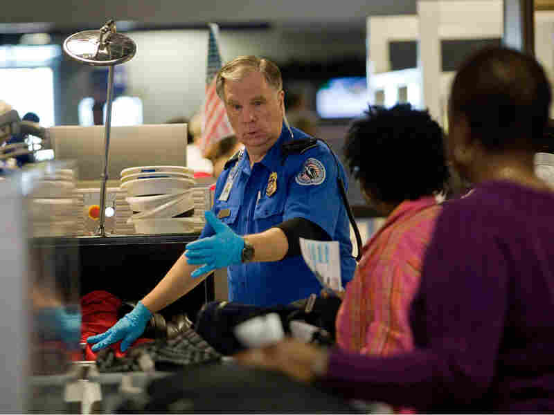 A TSA officer screens airline passengers at the Dallas/Fort Worth International Airport on Sunday.