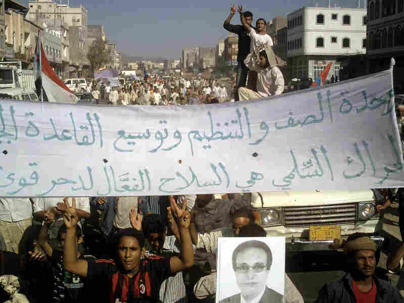 Yemeni protesters hold pro-al-Qaida banners and wave the victory sign.
