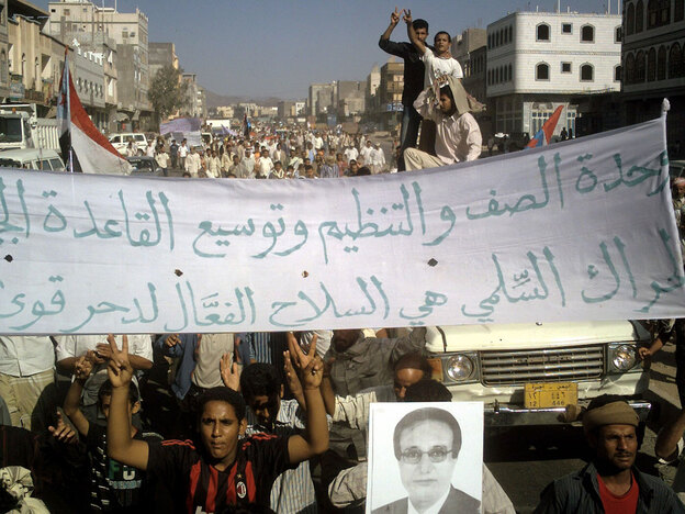 Yemeni protesters hold pro-al-Qaida banners and wave the victory sign during a demonstration in the Radfan district of Lahj in southern Yemen on Dec. 24.