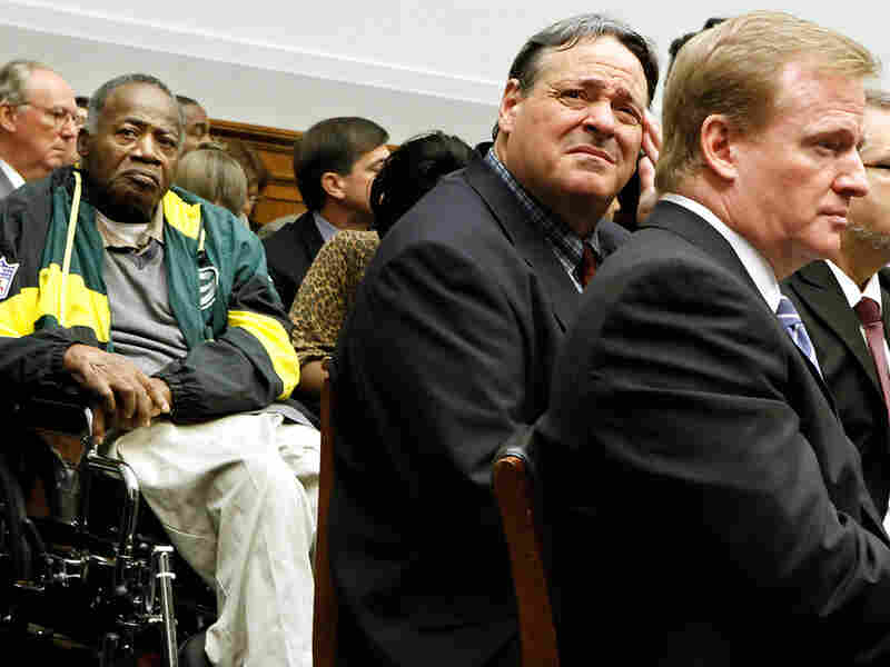 Former NFL player Brent Boyd rubs his head while sitting next to NFL Commissioner Roger Goodell.