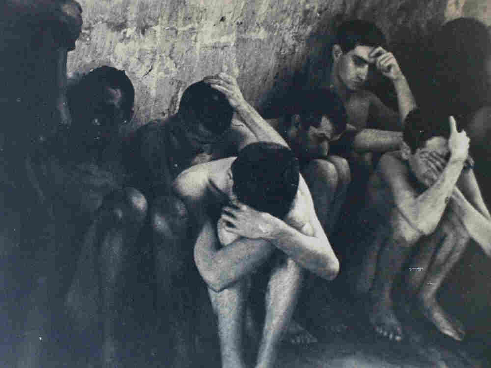 A photo of naked men huddled against a wall in the mental institution.