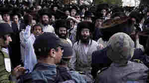 Ultra-Orthodox Jewish men protest behind a police line outside Intel's plant in Jerusalem.