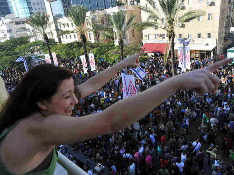 An Israeli woman cheers from her balcony to the crowds below during a street party in Tel Aviv.