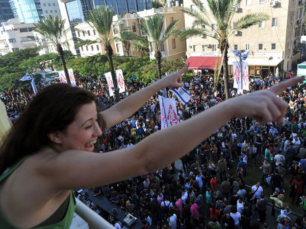 An Israeli woman cheers from her balcony to the crowds below during a street party in Tel Aviv on Dec. 25. The city's reputation as a liberal, international hot spot is growing.
