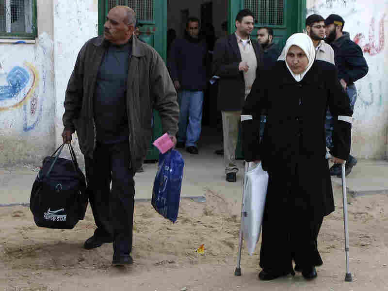 Palestinians arrive to cross into Egypt through the Rafah border crossing in the southern Gaza Strip