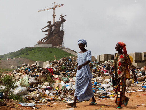 Women walk past rubbish heaps at the base of the Monument of the African Renaissance in Senegal.