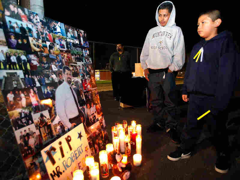 Students pause next to a photo of late Bobby Salcedo during a vigil on Monday.