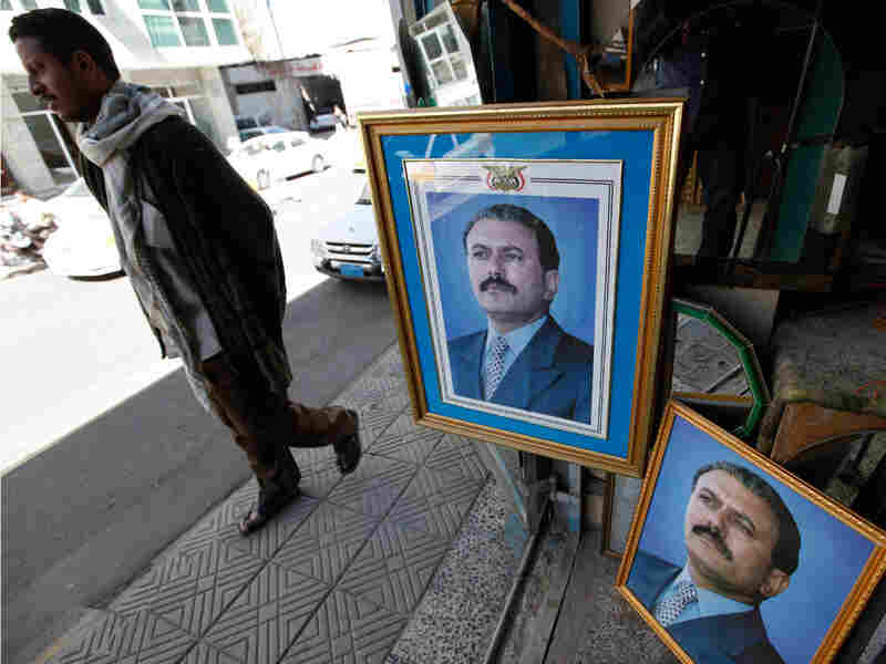 A Yemeni man passes framed pictures of Yemeni President Ali Abdullah Saleh