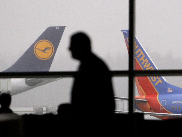 """A passenger walks past waiting jets at Seattle-Tacoma International Airport on Jan. 4. Dozens of names have been added to the government's terrorist watch lists and """"no fly"""" list after a failed terrorist attack on Christmas. (AP)"""